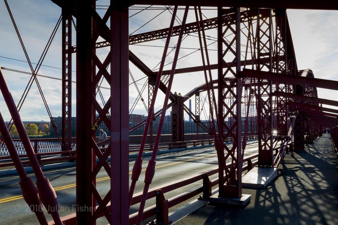 man walks across metal bridge